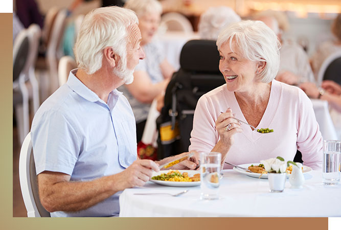 Senior couple having a meal at a table. Both are laughing.